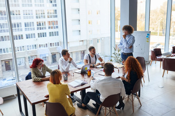 creative and enthusiastic business group sitting in office together working as team, wearing formal...