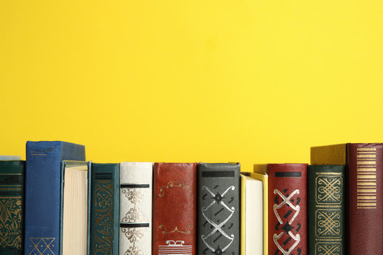 Collection of old books on yellow background, space for text