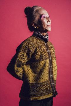 影になっている、柄模様のセーターを着たシニア女性のポートレート