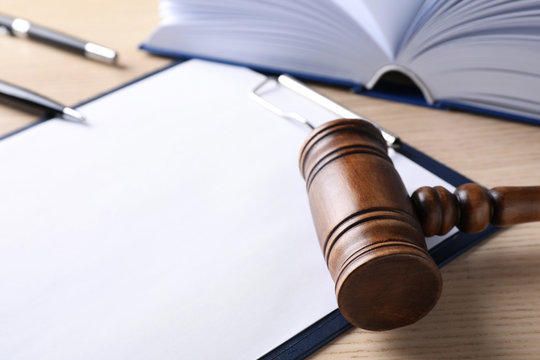 Clipboard with words DOMESTIC VIOLENCE and gavel on wooden table, closeup