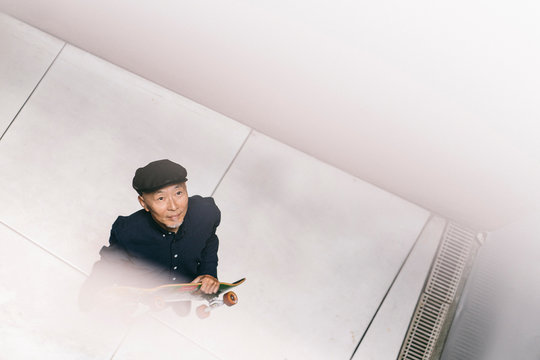 真上から見た、スケートボードを持ち、ハンチング帽を被ったシニア男性のポートレート