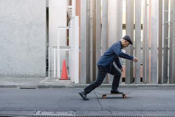 屋外でスケートボードに乗ろうとしている、ハンチング帽を被ったシニア男性のポートレート