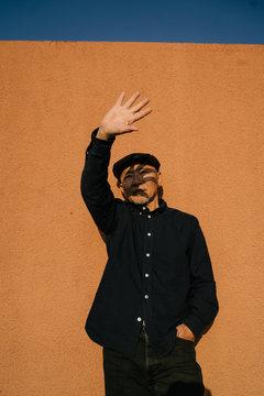屋外で壁に背にして立つシニア男性のポートレート