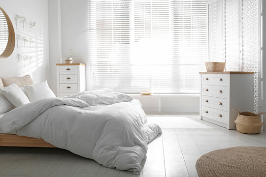 Stylish bedroom interior with white chest of drawers