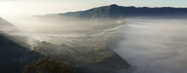 Mount Bromo active volcano in clouds during sunrise within the sea of sands in the Bromo-Tengger-Semeru National Park, Indonesia.