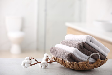 Basket with fresh towels on table in bathroom