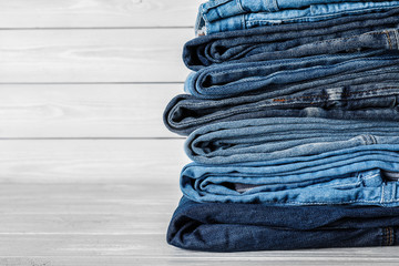Stack of different jeans on white wooden table. Space for text