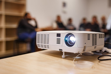 LCD video projector at business conference or lecture in a conference room or office with blurred people background