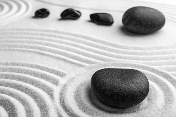 Photo sur Plexiglas Zen pierres a sable Black stones on sand with pattern. Zen, meditation, harmony