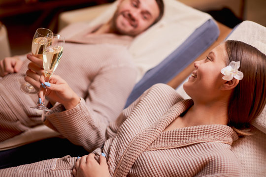 Beautiful caucasian couple in love relax spending time in spa center together, enjoy spa procedures, drinking champagne. isolated room