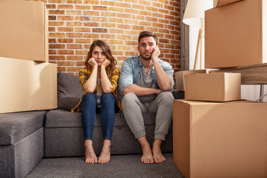 Confused couple of having to move and arrange all the packages. Concept of success, delusion, change and future