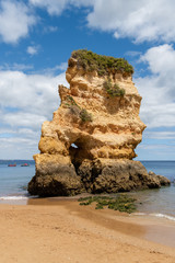 Tall rock formation and boats along a beach in the Algarve region of Portugal