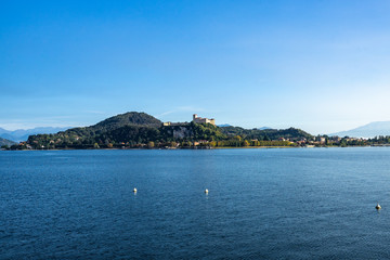 View of Rocca di Angera (Borromeo Castle) from Arona waterfront on the shores of Lake Maggiore, Piedmont, Italy.