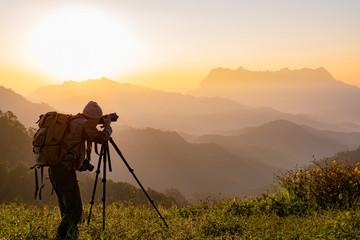 Nature photographer take photos with mirror camera on peak of mountain at morning sunrise