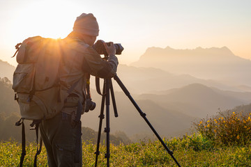 Nature photographer take photos with mirror camera on peak of mountain at morning sunrise
