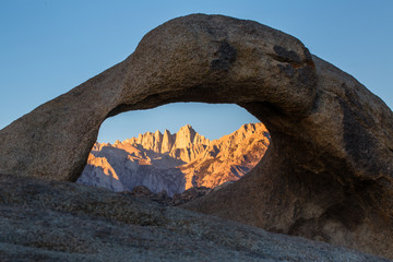 Mount Whitney in sunrise light through arch with clear sky overhead.