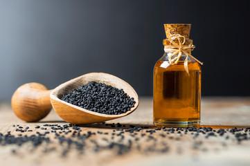 Fototapeta glass bottle of black cumin seeds essential oil , Nigella Sativa in spoon on wooden background. Organic herbal medicine for many diseases, black cumin obraz