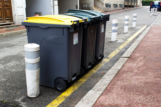 line of garbage can containers in city street