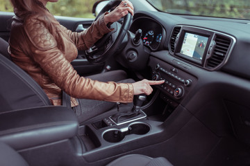 woman car interior includes button, application air conditioning selection, seat heating ventilation, automatic transmission, autumn spring forest park. Leather jacket. Screen with navigation.