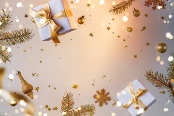 Merry Christmas and New Year background. Xmas holiday card made of flying decorations, gold fir branches, balls, snowflakes, sparkles, gift boxes, bokeh, light on golden background. Selective focus