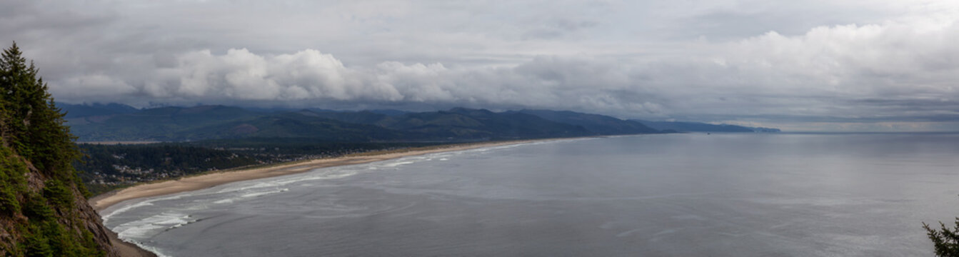 Manzanita, Oregon, United States. Aerial Panoramic View of a small town and a sandy beach on the the Pacific Ocean Coast during a cloudy summer day.