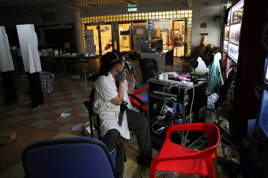 """A protester who calls himself """"Riot Chef"""", and who said he was a volunteer cook for protesters, smokes in a canteen in Hong Kong Polytechnic University (PolyU)"""