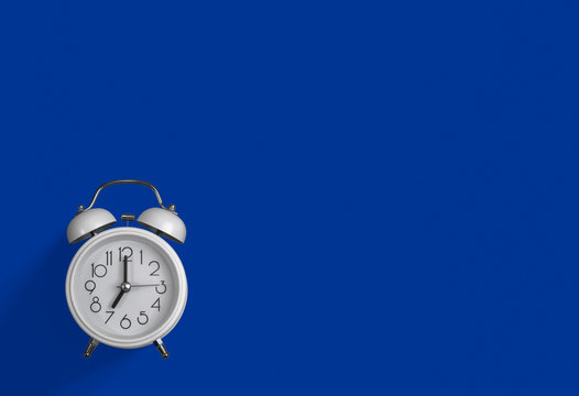a white alarm clock with a dark blue background.