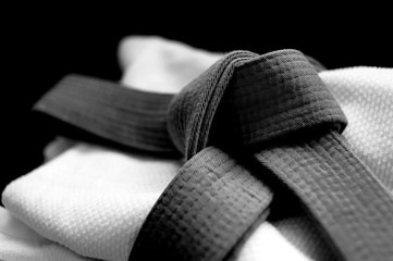 Black judo, aikido or karate belt on white budo gi. Concept is applicable to sports, business or education