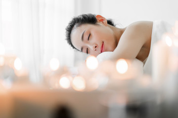 Beautiful young woman beauty skin treatment relaxing lying on towel in massaging and spa salon