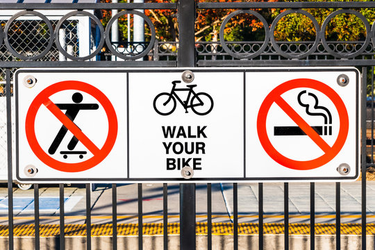Signs depicting the No Skateboarding, no Smoking and Walk your bike rules posted at a train station