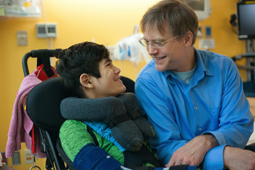 Father talking with disabled son in wheelchair at hopsital room