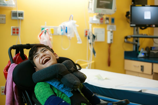 Disabled boy in wheelchair smiling next to hospital bed