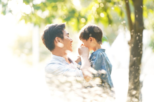 happy asian father and son having fun outdoors