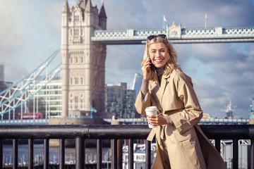 Portrait einer telefonierenden Geschäftsfrau mit Trenchcoat Mantel vor der Skyline von London