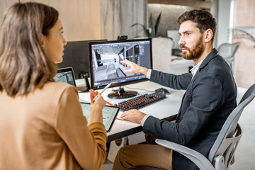 Two creative office employees making interior design on the computer and digital tablet at the modern office of architectural firm. Concept of 3d modeling and digital Interior designing
