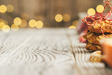 Oatmeal cookies on a old wooden background with cinnamon sticks and decorations