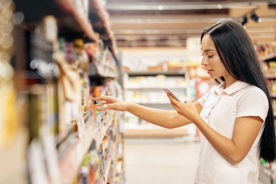 Young adult woman using smartphone and choosing food in supermarket