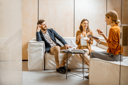 Young couple talking with woman as sales manager, financial advisor or psychotherapist, sitting on the comfortable couch in the office