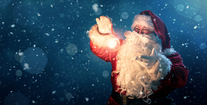 Happy Santa Claus holding glowing christmas ball over defocused blue background with copy space