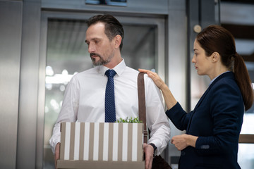 Office worker holding box while leaving the office after dismissal