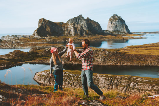 Happy family traveling with baby vacations outdoor couple mother and father holding up child adventure healthy lifestyle trip in Norway Helgeland islands landscape