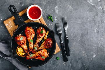 Roasted Lemon Chicken Legs with chili sauce and sesame in cast iron pan on dark stone background