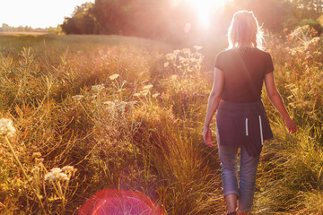 Beautiful young woman walking in field with sunrise