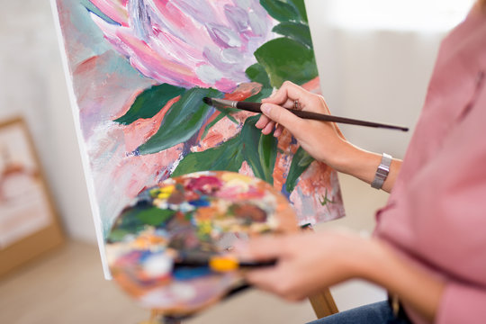 art, creativity and inspiration concept - female hands with paintbrush painting at home or studio