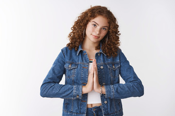 Serious-looking attractive caucasian redhead young girl student wearing denim jacket press palms together praying supplicating make wish asking favour begging help, standing white background