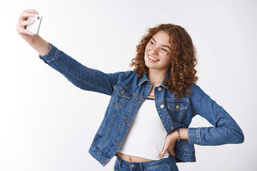 Friendly outgoing attractive young redhead curly girl pimples and freckles hold hand waist confident extend arm taking selfie new smartphone camera smiling gadget display standing white background