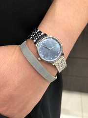 Silver metal watch with mother of pearl face and diamonds, stainless steel bangle bracelet on young woman's wrist