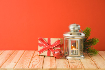 Christmas holiday background with candle lantern and gift box on wooden table.