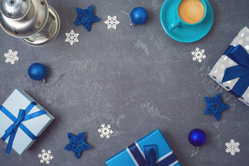 Christmas background with gift boxes and coffee cup on blackboard background.