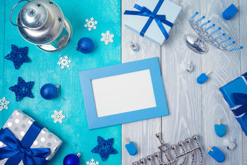 Christmas and Hanukkah celebration concept. Winter holidays background with photo frame, gift boxes and traditional decorations. Top view from above